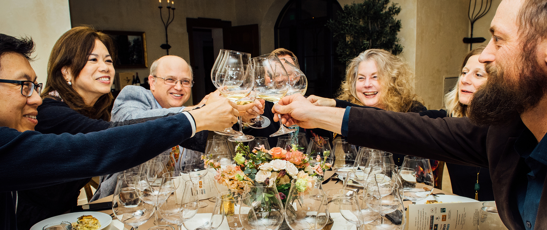 People toasting wine glasses over dinner