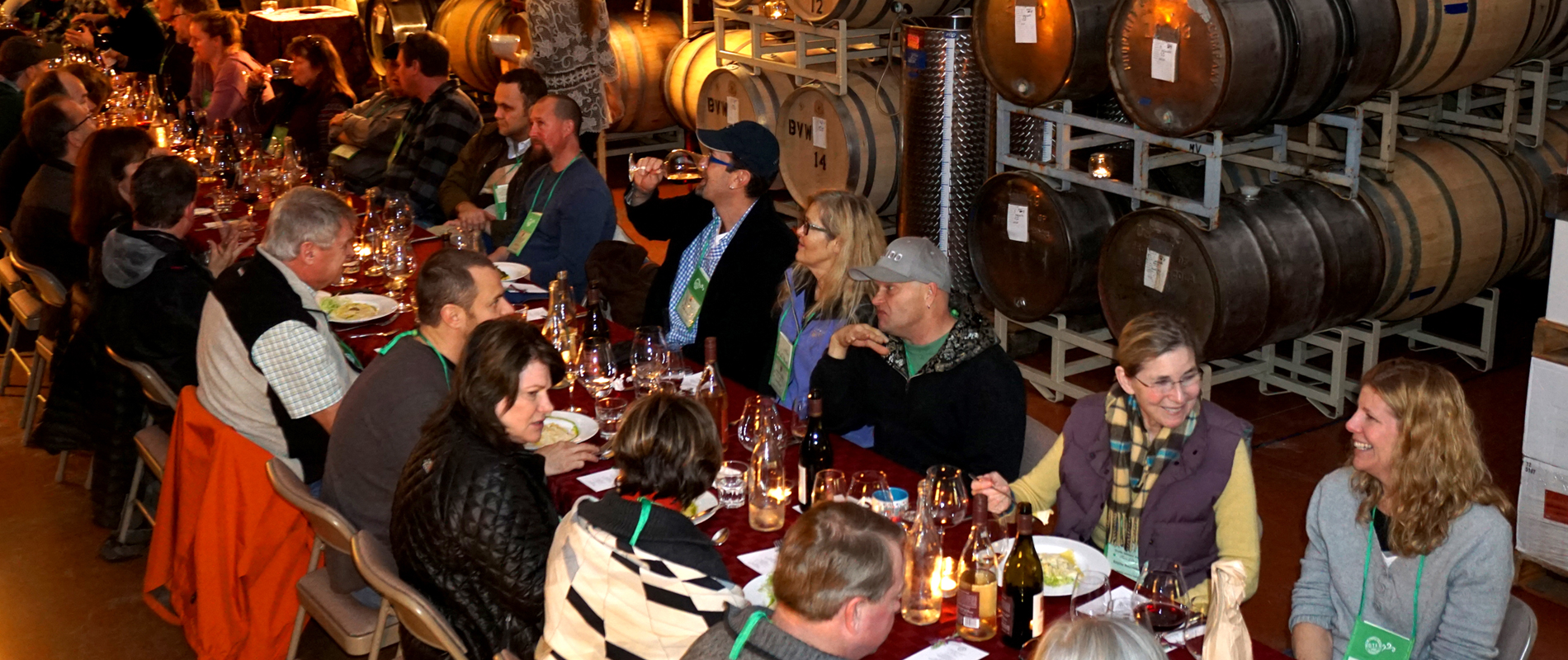 People seated for dinner in the barrel room of a winery