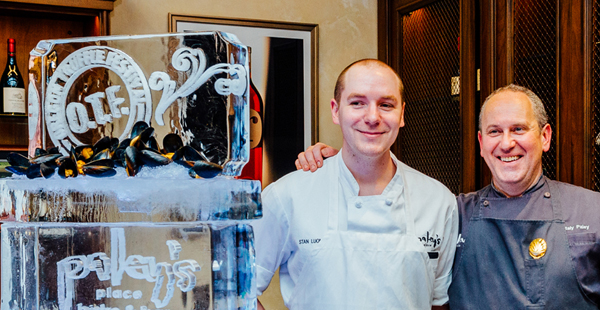 Two men posing with an ice sculpture of the Oregon Truffle Festival logo