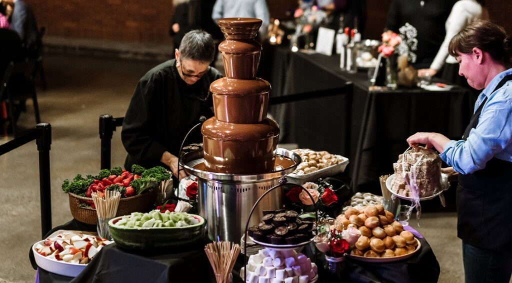 Preparing the Chocolate Fondue Fountain for Valentine's Food is Love! event. – Photo by Reagan Kastner