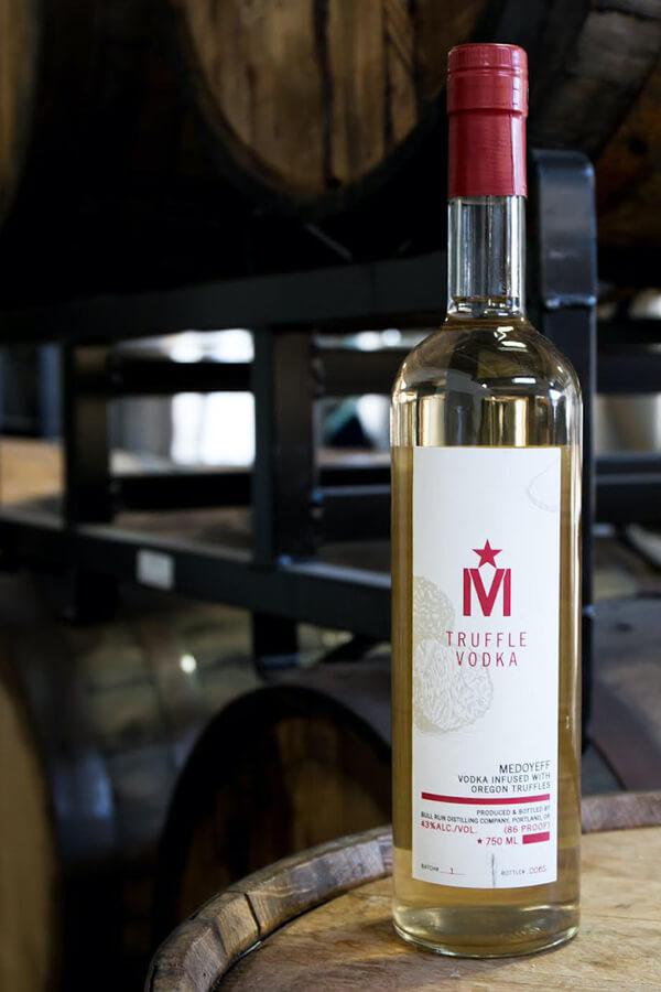 A bottle of Medoyeff Truffle Vodka sitting on an aging barrel in a barrel room.