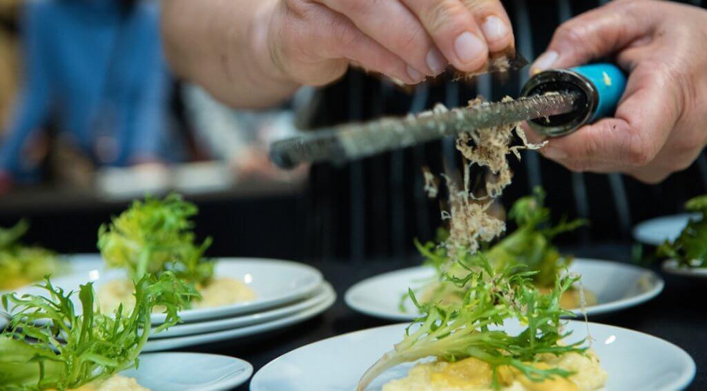 Chef Emily Lesiak puts the final touch of fresh Oregon truffles on her demo dish: Creamy Truffled Polenta with Pecorino & Roasted Butternut Cream Sauce and Oregon Black Truffle